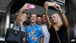 俄罗斯总理梅德维耶夫在参加东盟峰会后和俄罗斯与乌克兰游客合影(2015年11月22日)