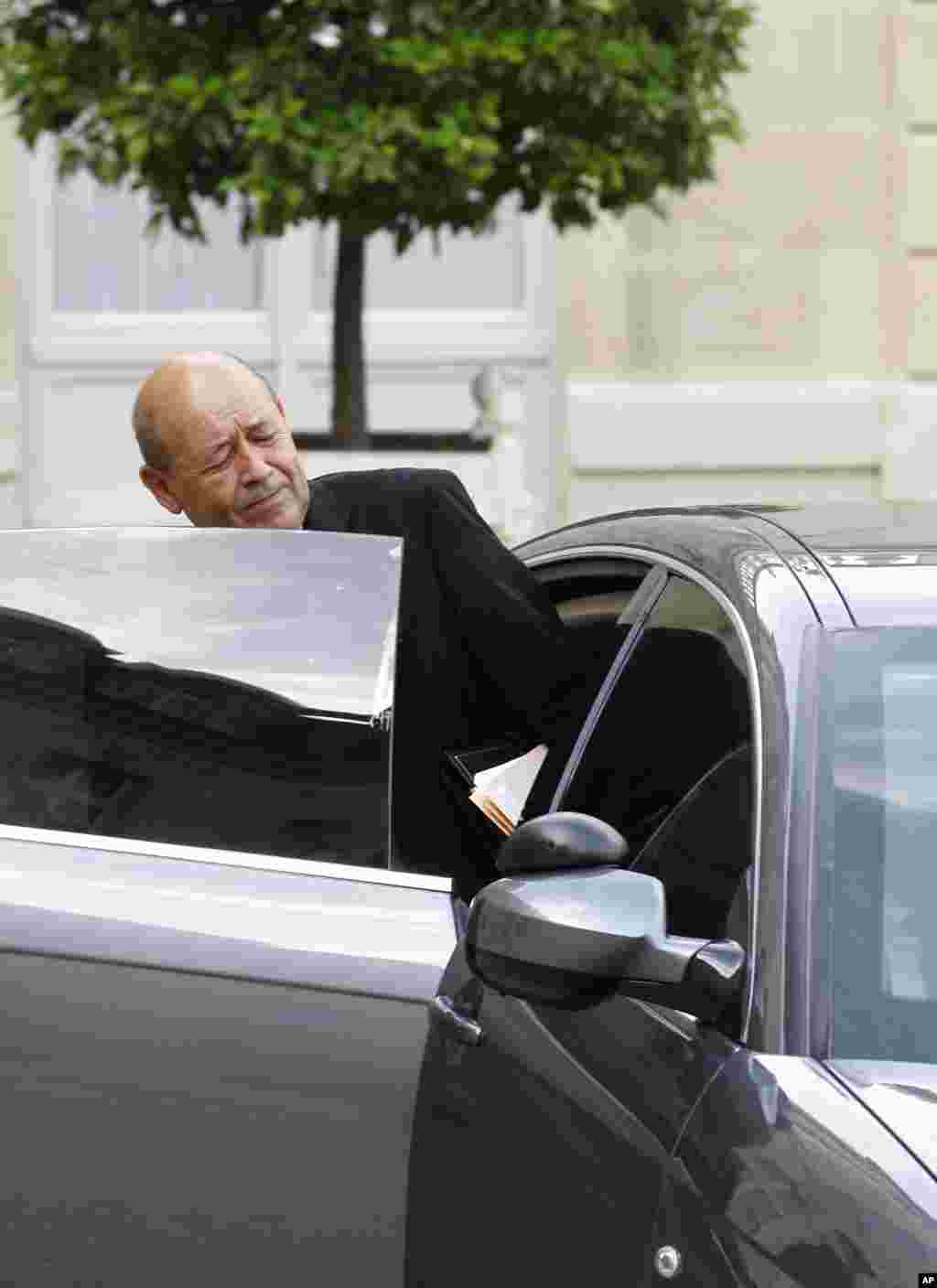 French Defense Minister Jean-Yves Le Drian gets into his car, as he leaves the Elysee Palace following a special defense meeting with French President Francois Hollande in Paris, Sept. 25, 2014.