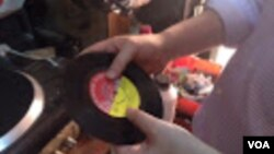 Melodica Music Store owner Abdul Karim plays a 45 RPM album recorded at the store years ago. (VOA / G. Joselow)