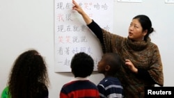 Teacher Kennis Wong (R) points to Chinese characters on a board at Broadway Elementary School in Venice, Los Angeles, California, Apr. 11, 2011.
