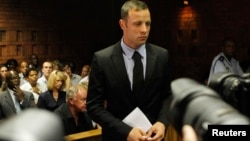 Oscar Pistorius stands in the dock during a break in court proceedings at the Pretoria Magistrates court, February 20, 2013.