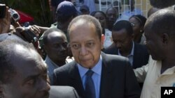 Former Haitian dictator Jean-Claude Duvalier, center, leaves Canape Vert Hospital in Port-au-Prince, Haiti, March 29, 2011