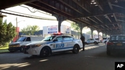 FILE - New York City police secure the scene where two men were shot as they left prayers at a mosque.