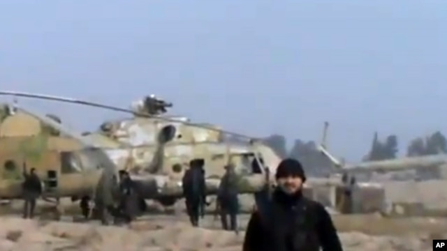 In this image taken from video obtained from the Ugarit News, which has been authenticated based on its contents and other AP reporting, Syrian rebels capture a helicopter air base near the capital Damascus after fierce fighting in Syria, on Sunday, Nov.