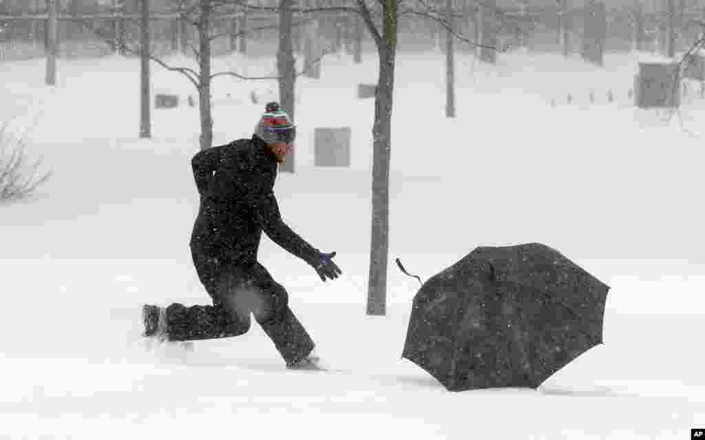 A man chases his blowing umbrella during a winter snowstorm in Boston, Jan. 27, 2015. A blizzard heaped snow on Boston, the rest of eastern Massachusetts and parts of Long Island, delivering wind gusts topping 75 mph.
