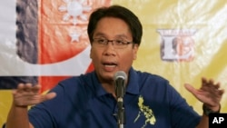 FILE - Mar Roxas gestures as he answers questions from reporters in suburban Quezon City, north of Manila, Philippines.