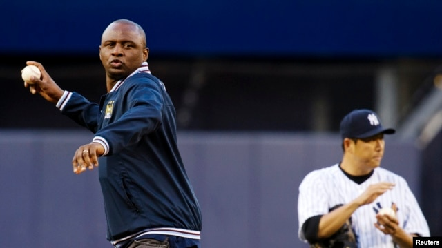 Patrick Vieira, left, head of the elite development squad at Manchester City Football Club, throws out the ceremonial first pitch near New York Yankees' Hiroki Kuroda, Yankee Stadium, New York, May 17, 2013.