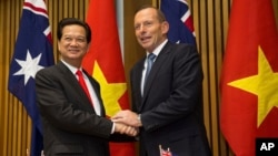 "Vietnamese Prime Minister Nguyen Tan Dung and his Australian counterpart Tony Abbott shake hands before witnessing the signing of a ""friendship agreement"" between their countries at Parliament House in Canberra, Australia, March 18, 2015."