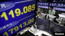 Employees of a foreign exchange trading company work under monitors displaying the exchange rates between the Japanese yen and the U.S. dollar. Japan's efforts to start economic growth have caused its currency, the yen, to rise in value against the dollar.