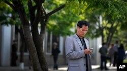 지난 2015년 5월 평양 거리에서 한 남성이 손전화를 사용하고 있다.