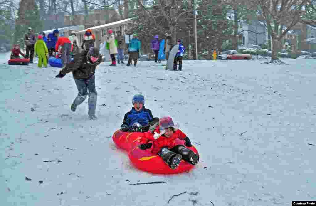 Trẻ em chơi trượt tuyết trong công viên trong một cơn bão tuyết ở Crystal City, Arlington, bang Virginia, Mỹ, ngày 21 Ttháng 1, 2014. (Ảnh của Dimitris Mantis/ VOA)