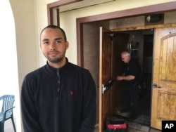 Drew Williams, a member of the Eugene Islamic Center, poses for a portrait outside the building in Eugene, Oregon, as locksmith Jim King upgrades the locks on the front doors, June 1, 2017.