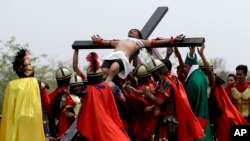 Devotees dressed as Roman soldiers lift Ruben Enaje on the cross after he was nailed to it for his 32nd time during a re-enactment of Jesus Christ's sufferings as part of Good Friday rituals in the village of San Pedro Cutud, Pampanga province, northern Philippines, March 30, 2018.