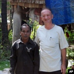 Linguist and S'aoch scholar Jean-Michel Filippi (right) stands in the village with Mr. Tuem, the son of the village chief. Mr. Tuem is one of just 10 villagers who is fluent in the S'aoch language, 19 Jan 2010