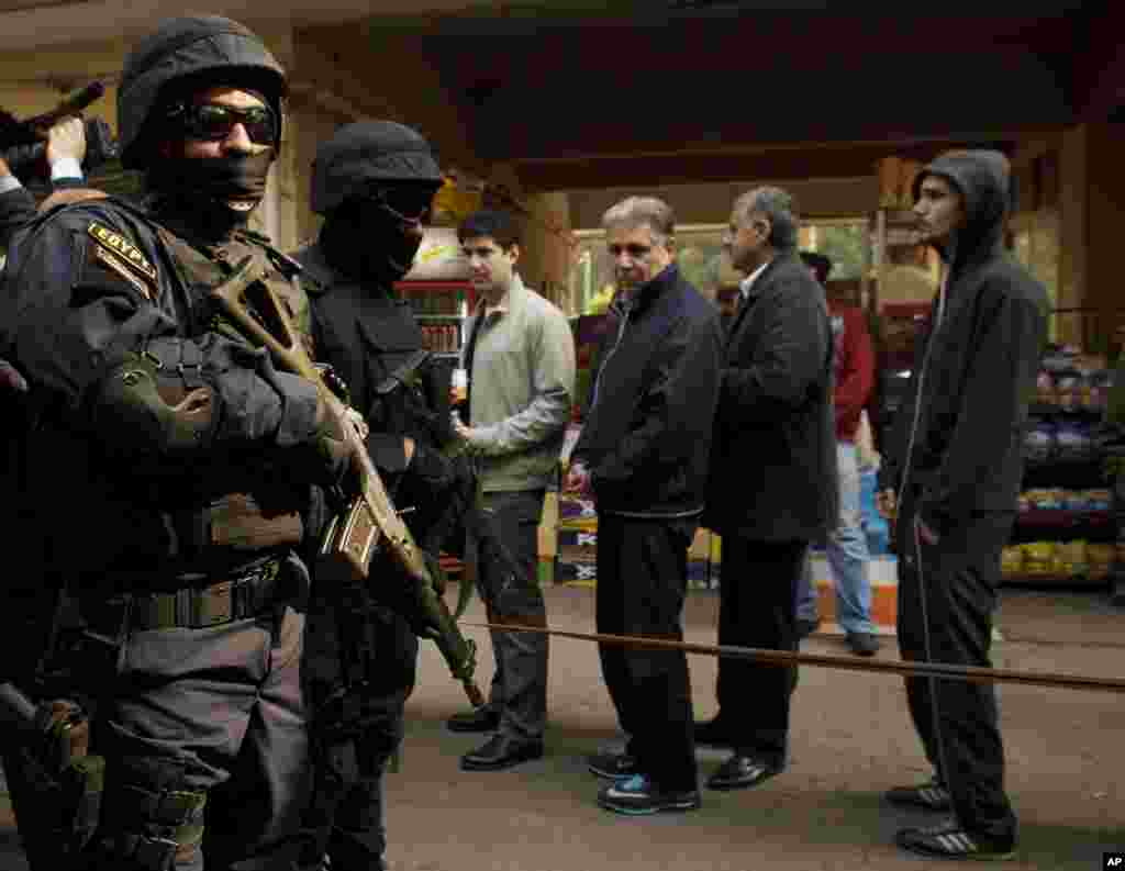Members of the Egyptian Interior Minister's security detail stand guard as voters line up at a polling station on the first day of voting in the country's constitutional referendum in the Zamalek neighborhood in Cairo, Jan. 14, 2014.