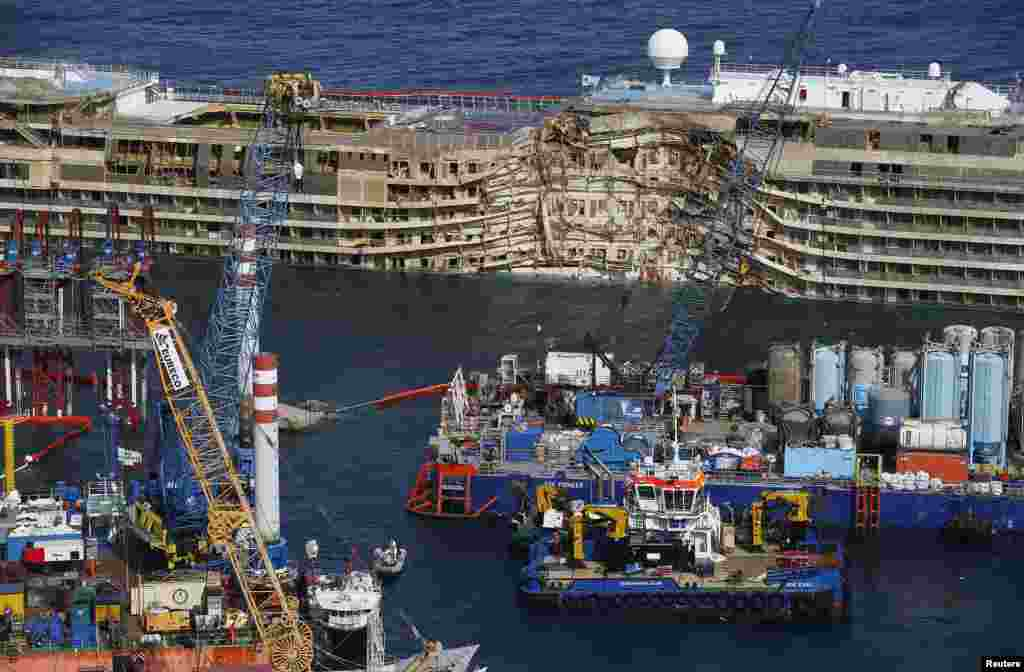 "The capsized cruise liner Costa Concordia is seen at the end of the ""parbuckling"" operation outside Giglio harbor. Salvage crews completed raising the wreck of the Costa Concordia after a 19-hour-long operation on the Italian island of Giglio where the huge cruise liner capsized in January last year."