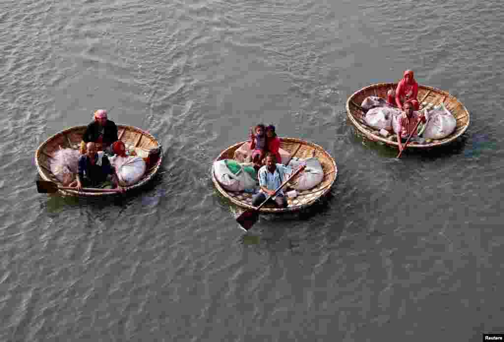 Para nelayan mendayung 'perahunya' untuk membawa keluarganya di danau Vembanad di kota Kochi, India.