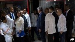 El presidente de Cuba, Miguel Díaz-Canel, en el centro, habla con los médicos cubanos a su regreso de Brasil en La Habana (AP Foto / Desmond Boylan)