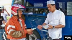 Seorang warga sedang menukarkan uang tunai di layanan Drive Thru Bank Indonesia (foto: VOA).