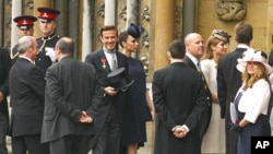 Soccer star David Beckham (C) and his wife Victoria arrive at Westminster Abbey before the wedding of Britain's Prince William and Kate Middleton, in central London April 29, 2011.