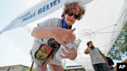 Salvation Army volunteer Dyane Welt pulls bottles of water from an ice cooler at a hydration station in an effort to beat the rising temperatures expected to hit 115 degrees in Phoenix, June 20, 2016.