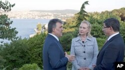 Turkish President Abdullah Gul (L) speaks with US Secretary of State Hillary Clinton and Turkish Foreign Minister Ahmet Davutoglu in front of the Bosphorus Sea in Istanbul, July 15, 2011