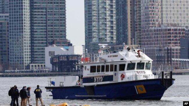 Personal de NTSB, la Junta Nacional de Seguridad en el Transporte, observa el lunes, 12 de marzo de 2018, el lugar donde se sumergió el helicóptero en el East River de Nueva York el domingo.