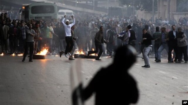 Egyptian anti-government activists throw stones at riot police during clashes in Cairo, Egypt, Jan. 26, 2011.