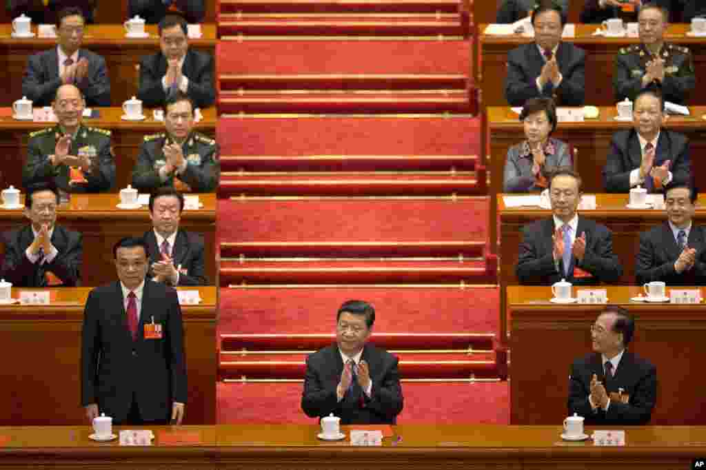 Li Keqiang stands up when he was announced to be China's new premier, while Chinese President Xi Jinping and former Chinese Premier Wen Jiabao clap at Beijing's Great Hall of the People, March 15, 2013.