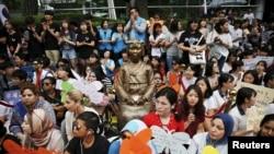 """2015年7月22日,韩国首尔的抗议者们围坐在一尊""""慰安妇""""塑像边,要求日本政府道歉并赔偿。"""