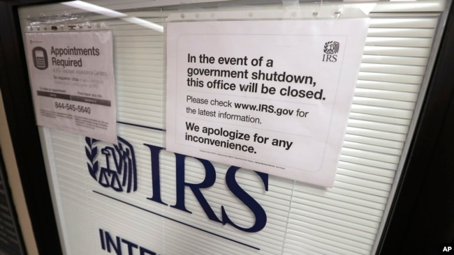 FILE - Doors at the Internal Revenue Service in the Henry M. Jackson Federal Building are locked and covered with blinds as a sign posted advises that the office will be closed during the partial government shutdown in Seattle, Jan. 16, 2019.