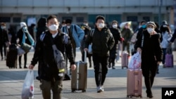 Travelers wear face masks as they walk outside the Beijing Railway Station in Beijing, Saturday, Feb. 15, 2020. (AP Photo/Mark Schiefelbein)