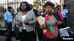 Kenyan members of parliament Gladys Wanga, left, and Christine Mbaya leave the National Assembly to protest the approval of new anti-terrorism laws in Kenya's capital Nairobi, Dec. 18, 2014.