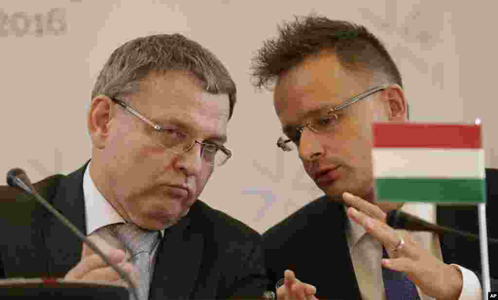 Czech Republic's FM Lubomir Zaoralek, left, talks to Hungarian FM Peter Szijjarto during a press conference as the Visegrad Group foreign ministers meet their counterparts from Germany and Luxembourg to talk about the current migration crisis in Prague, Czech Republic.