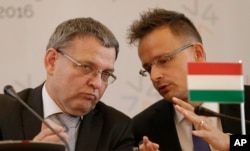 Czech Republic's FM (L) talks to Hungary's foreign minister Peter Szijjarto during a press conference as the Visegrad Group foreign ministers meet their counterparts from Germany and Luxembourg, Sept. 11, 2015.