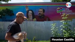 Un nicaragüense camina frente a un pancarta con la imagen del presidente Daniel Ortega y la primera dama Rosario Murilllo. [Foto Houston Castillo/VOA].