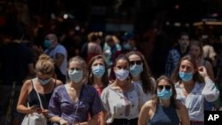 Tourists wearing face masks wait to cross a road in downtown Barcelona, Spain, Thursday, July 16, 2020. With Europe's summer vacation season kicking into high gear for millions weary of months of lockdown, scenes of drunken British and German…