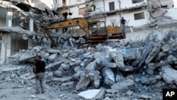 Workers remove the rubble of a building destroyed by an Israeli airstrike, in Gaza City, Tuesday, June 15, 2021. The building was damaged last month during an 11-day war between Israel and the Hamas militant group that rules Gaza. (AP Photo/Adel…