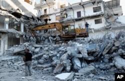 Pekerja memindahkan puing-puing bangunan yang hancur akibat serangan udara Israel, di Kota Gaza, Selasa, 15 Juni 2021. (Foto: AP)