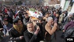 Pelayat yang berduka membawa jenazah pemberontak Suriah yang tewas di Idlib, Suriah ke tempat pemakaman (12/2).