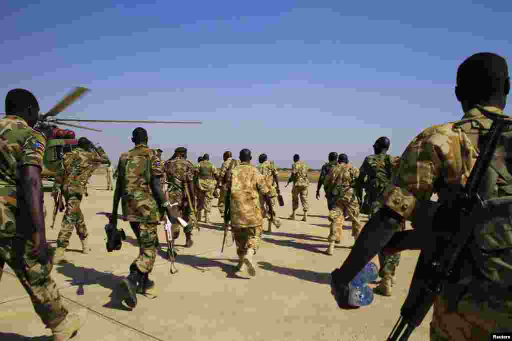 South Sudan army soldiers walk to board a military helicopter at Juba international airport, before heading to Bor, Dec. 25, 2013.