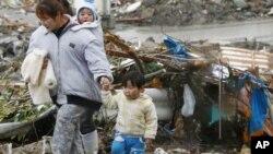 日本灾民经过被地震摧毁的家