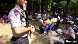 Polisi menjaga warga Kristiani di desa Suka Makmur, kabupaten Singkil, provinsi Aceh yang melakukan misa di lapangan terbuka pasca kerusuhan di Singkil tahun lalu, Minggu 18 Oktober 2015 (foto: dok).