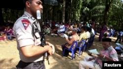 Seorang polisi memegang senjata dan berjaga-jaga sepanjang kebaktian Minggu di samping gereja yang dibakar di desa Suka Makmur di Singkil, Aceh, 18 Oktober 2015. (REUTERS/YT Haryono)
