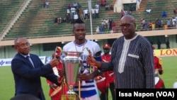Le président de la CAF, Ahmad Ahmad (à g.), et le président du Burkina Faso, Roch Kaboré (à dr.), ont remis la Coupe du Faso au capitaine d'EFO, Ouagadougou, le 5 août 2017. (VOA/Issa Napon)
