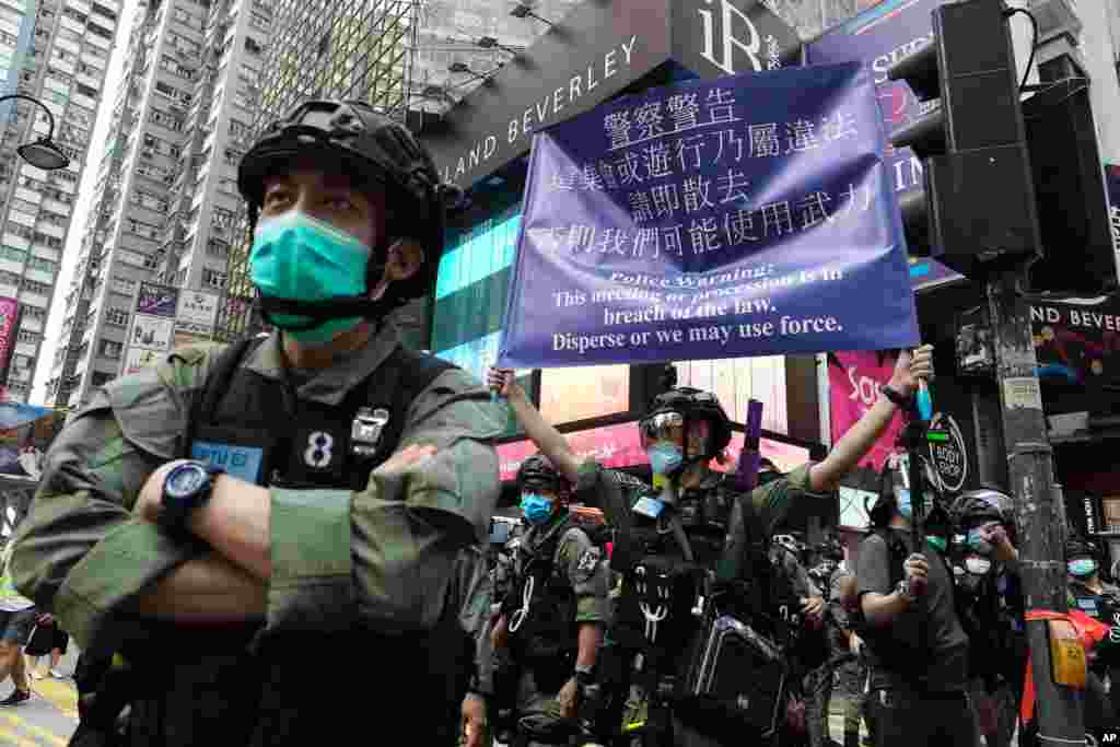 A police officer shows a warning sign on China's National Day in Causeway Bay, Hong Kong.