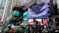 在中國共產黨建立政權週年紀念日,一名警察在香港銅鑼灣打出警告旗。 (2020年10月1日)