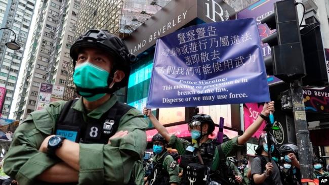 在中国共产党建立政权周年纪念日,一名警察在香港铜锣湾打出警告旗。(2020年10月1日)