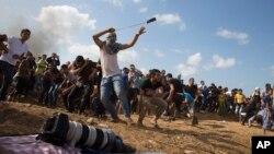 Người biểu tình Palestine ném đá vào binh sĩ Israel trong cuộc đụng độ ở biên giới, 9/10/2015.