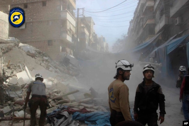 FILE - In this picture provided by the Syrian Civil Defense group known as the White Helmets, Syrian Civil Defense workers search through the rubble in rebel-held eastern Aleppo, Syria, Oct. 12, 2016.